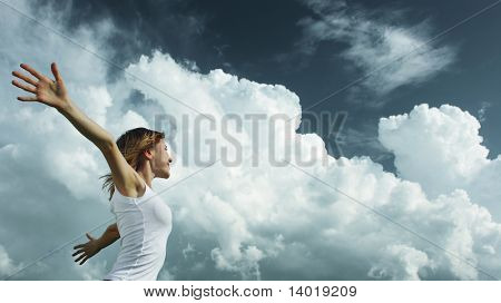 Young woman with raised hands over cloudy background