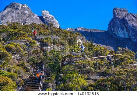 Mount Kinabalu,Ranau,Borneo-March 13.2016:Undentified of climber relaxing on the wooden stairs & enjoying the amazing view of the Ranau and Kundasang town from viewpoint Mountain Kinabalu.
