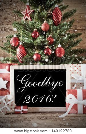 Nostalgic Christmas Card For Seasons Greetings. Christmas Tree With Balls. Gifts Or Presents In The Front Of Wooden Background. Chalkboard With English Text Goodbye 2016