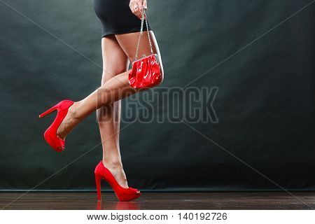 Celebration disco and evening fashion concept. Woman in black short dress red spiked shoes holding handbag bag part of body female legs in high heels on party floor