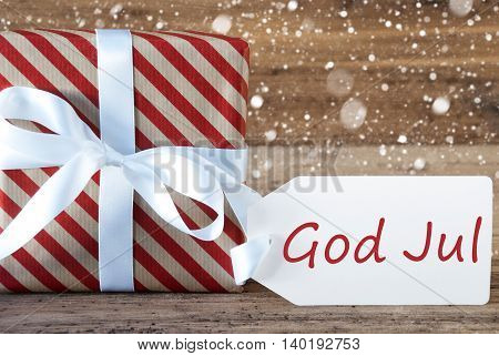 Christmas Gift Or Present On Wooden Background With Snowflakes. Card For Seasons Greetings. White Ribbon With Bow. Swedish Text God Jul Means Merry Christmas