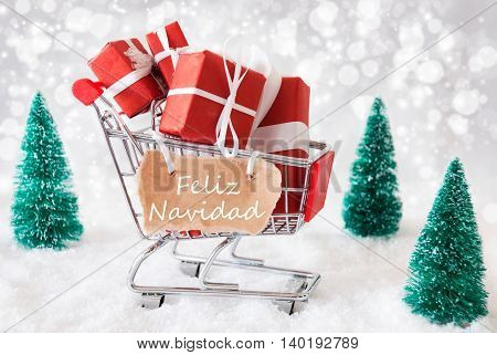 Trollye With Christmas Presents Or Gifts. Snowy Scenery With Snow And Trees. Sparkling Bokeh Effect. Label With Spanish Text Feliz Navidad Means Merry Christmas