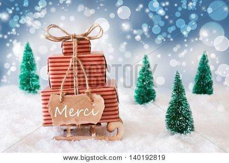 Sleigh Or Sled With Christmas Gifts Or Presents. Snowy Scenery With Snow And Trees. Blue Sparkling Background With Bokeh Effect. Label With French Text Merci Means Thank You