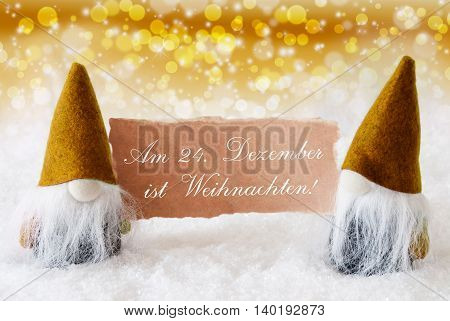 Christmas Greeting Card With Two Golden Gnomes. Sparkling Bokeh And Noble Background With Snow. German Text Weihnachten Means Christmas
