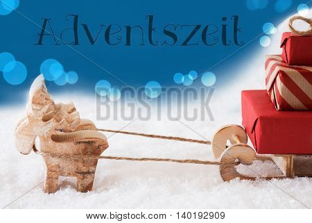 Moose Is Drawing A Sled With Red Gifts Or Presents In Snow. Christmas Card For Seasons Greetings. Blue Background With Bokeh Effect. German Text Adventszeit Means Advent Season