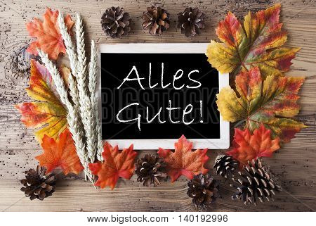 Blackboard With Autumn Or Fall Decoration. Greeting Card For Seasons Greetings. Colorful Leaves, Fir Cone And Barley On Aged Wooden Background. German Text Alles Gute Means Best Wishes