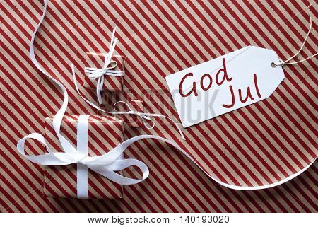 Two Gifts Or Presents With White Ribbon. Red And Brown Striped Wrapping Paper. Christmas Or Greeting Card. Label With Swedish Text God Jul Means Merry Christmas