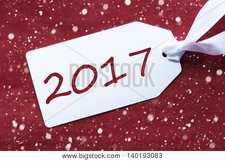 One White Label On A Red Textured Background. Tag With Ribbon And Snowflakes. English Text 2017 For Happy New Year Greetings