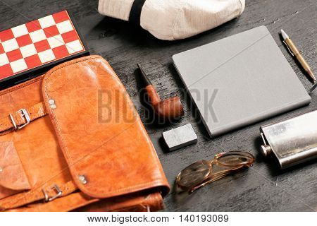 Selective focus on holiday set of a traveler - sunglasses, notebook, pen, leather bag, white hat, smoking pipe chessboard for fun