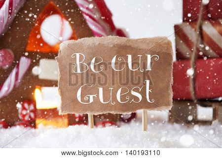 Gingerbread House In Snowy Scenery As Christmas Decoration. Sleigh With Christmas Gifts Or Presents And Snowflakes. Label With English Text Be Our Guest