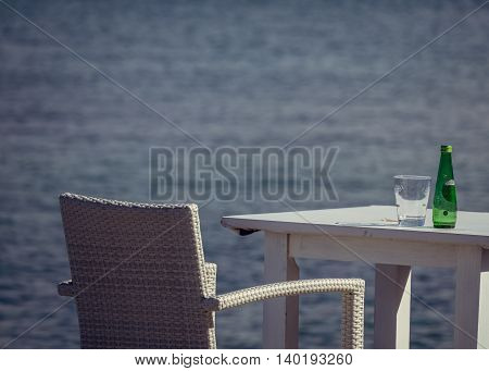 Empty glass and a bottle of still water on an outdoor table at a seaside resort in Canary Islands