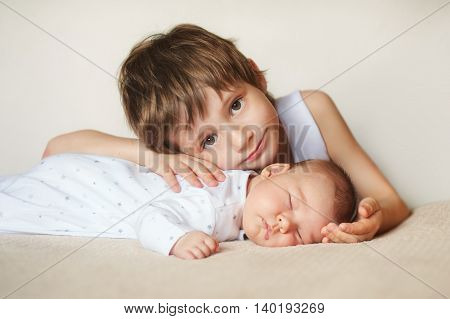 charming little brother and sister asleep embracing