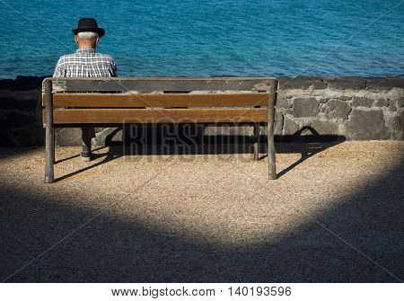 Old lonely man sitting alone on a wooden bench on a seaside promenade in summer