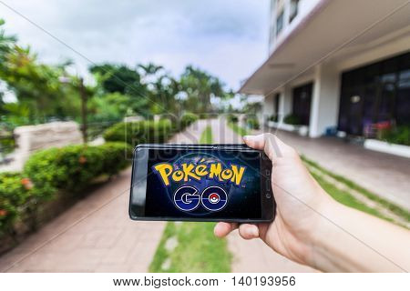 California, United States - July 16, 2016: Hand holding a cellphone to play Pokemon Go with blur garden background