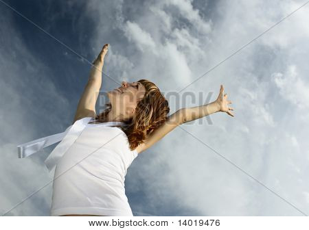 Young smiling woman with raised hands over blue sky