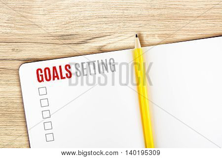 Goals Setting word on notebook lay on wood tableTemplate mock up for adding your goal.