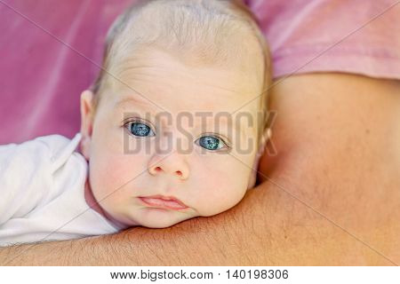 Portrait Of Cute 4-Month Newborn Baby Lying On Father Arms