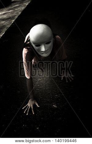 Mysterious woman wearing white mask crawling on the floor,Scary background for halloween