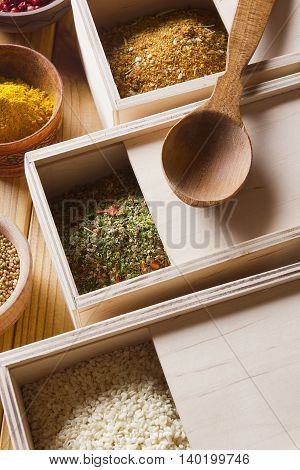 Set of spices in wooden boxes on a wooden table