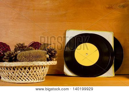 Basket with potpourri and vinyl records on a wooden background