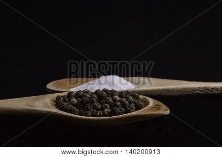 Salt and pepper corns on wooden spoons on a black background