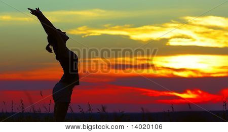 Young woman doing exercises under sunset light