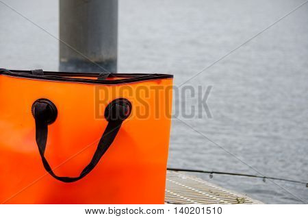 Orange Bag And Fishing Pole On A Dock
