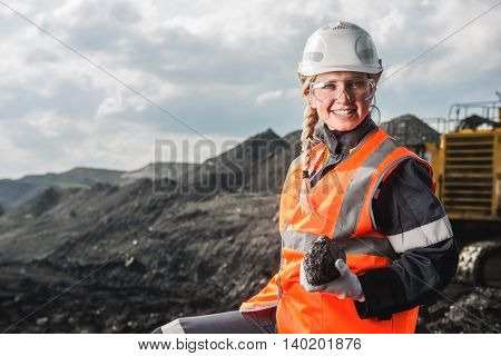 Young beautiful female holding a piece of coal