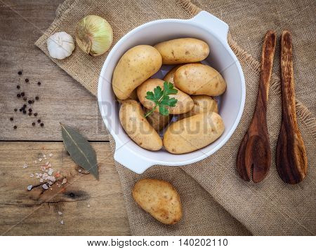 Fresh Organic Potatoes In White Ceramic Bowl With Ingredients And Herbs , Parsley, Garlic, Bay Leave