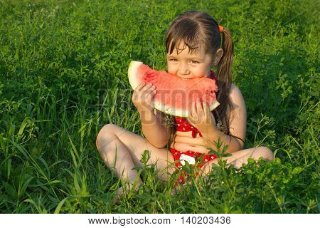 little white girl children in swimsuit sit on grass and hold watermelon