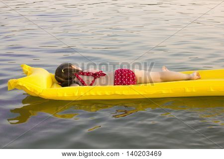 little white girl children lay on yellow inflatable mattress on lake