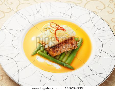 Fried pork ribs with asparagus on white plate in asian restaurant