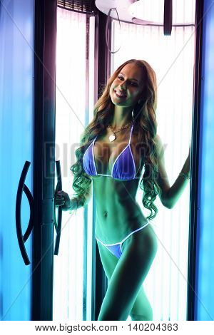 Photo of busty woman posing in tanning booth