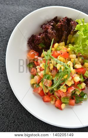 Special salad with corn tomato and herbs on white plate in restaurant