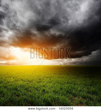 Storm dark clouds and light over field with green grass