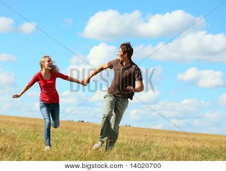 Young laughing couple running on meadow holding each other hands