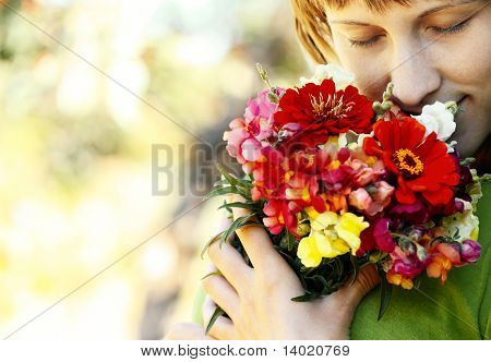 Young smiling woman with closed eyes and flowers bouquet