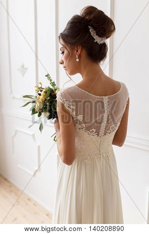 Bride portrait from the back holding a bouquet