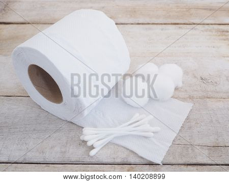 Tissue paper cotton ball and cotton buds on wooden background