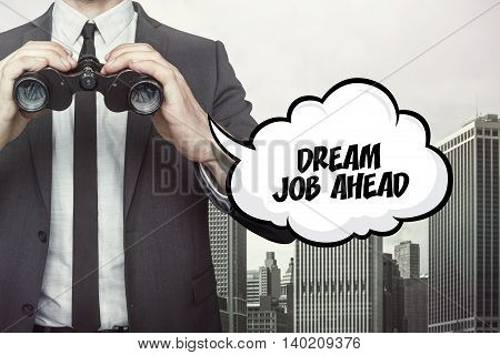 Dream job ahead text on speech bubble with businessman holding binoculars on city background