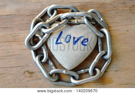 iron chain roll over heart stone on wooden board