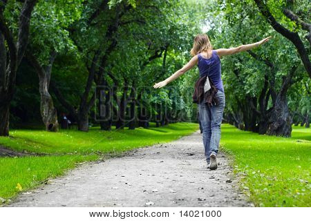 Woman walking on path in green summer park