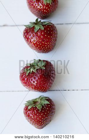 Strawberries on the white, wooden table