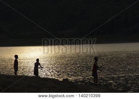 Children fishing by the lakeside and sunset view.