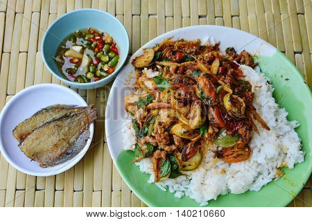 spicy stir-fried mussel on rice eat couple with fish fry