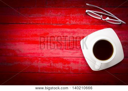 Background coffee cup and glasses on wooden red table background with black border.