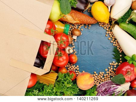 Paper bag with food on blue surface with copy space top view