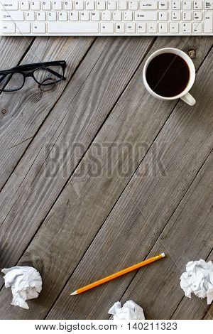 Cup Of Coffee Keyboard Glasses Crumpled Paper And Pencil On Wooden Table In A Home Office Top View. Business Background