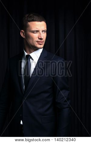 Handsome businessman isolated on black