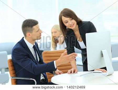 Smiling businesswoman showing something on computer as colleague